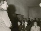 Assemblea, un militare parla a un gruppo di uomini in una sala adibita a scuola guida.